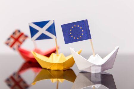 59144748-nave-di-carta-con-la-bandiera-europea-e-scozzesi-rotto-bandiera-britannica-dietro-concetto-di-spediz.jpg